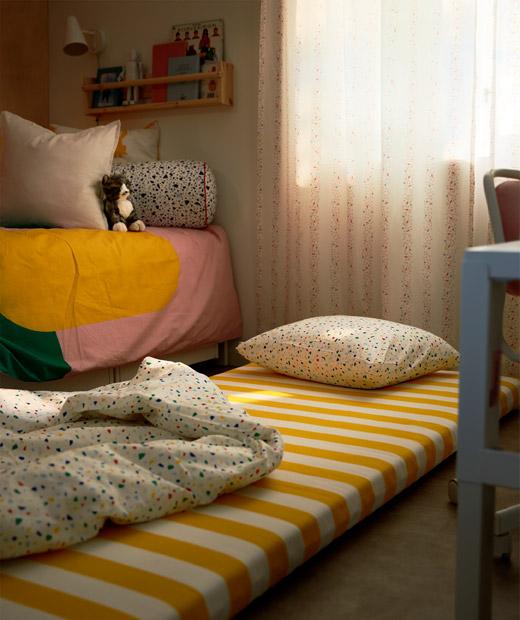 鋪在地上的床褥放有枕頭和被,旁邊是兒童睡床,房間燈光昏暗,拉上窗簾。