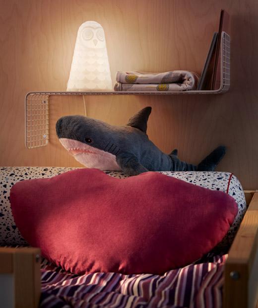 高架床尾放有咕𠱸、枕頭和鯊魚毛公仔,後面的簡約牆架上放有夜燈、書本和被。