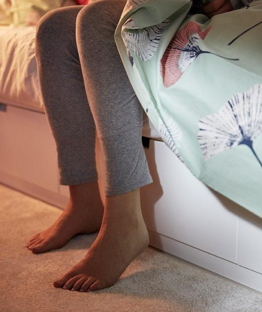 睡床的下半部,床架內置貯物箱,有一雙腳踏在長毛地氈上。