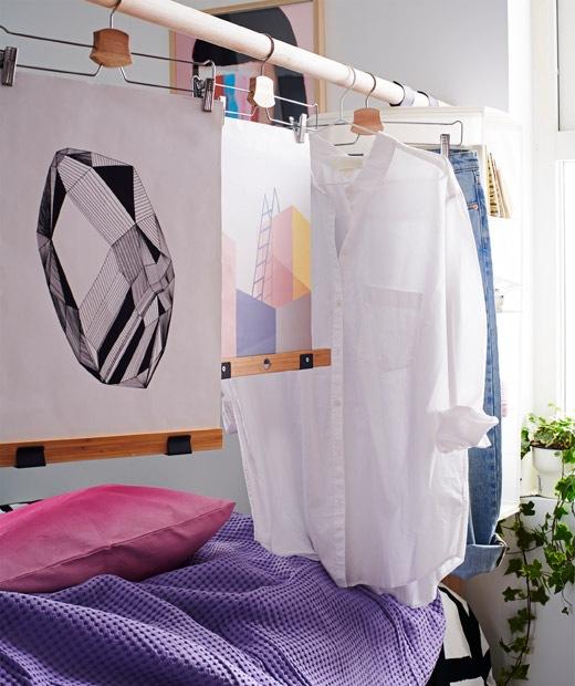 由一支升高的木桿構成的床頭板,用衣架掛上衣物和畫作,變成房間屏風。