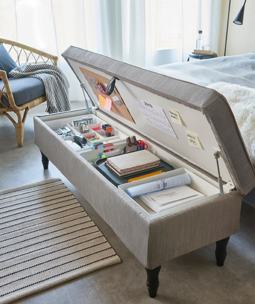 Textile-covered, combined bench and storage unit by a bed's foot end, lid up, holding the contents of a typical home office.