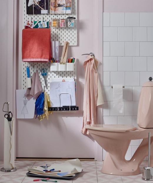浴室門後掛有洞洞板,上面收納了筆和畫紙等物品,廁所旁邊放有紙和筆。