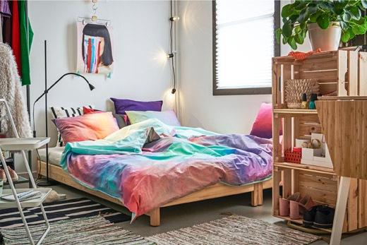房間一角放有一張鋪好的矮身雙人床,旁邊放有木箱製成的書架和衣帽架。