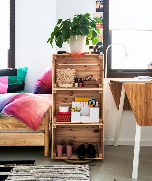 以三個木箱製成的書架,裡面放了少量物品,疊起放在睡床和小餐檯之間。