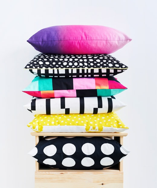 Cushions – black and white, graphic patterns, sharp colouring in a mix – piled in a stack on top of  a chest of drawers.
