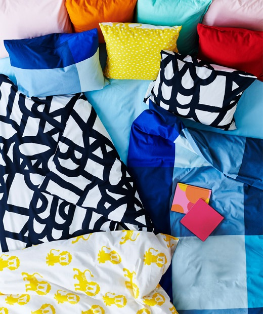 睡床上鋪滿圖案奪目的鮮色羽絨被、咕𠱸和布藝產品。
