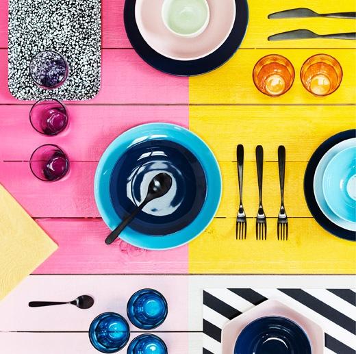 鮮豔套目的拼色表面,放滿不同顏色的碗、餐具和玻璃器皿。