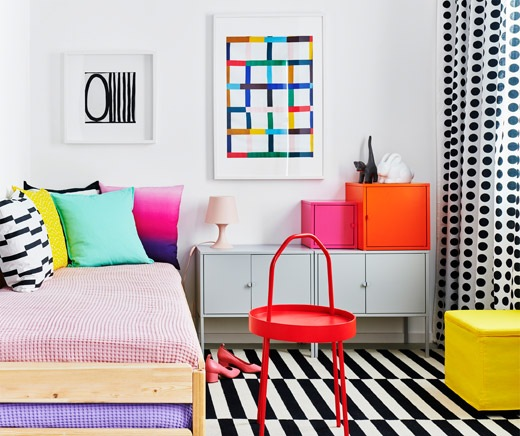 Bedroom furnished in a style characterised by block colouring and graphic patterns. Bed with cushions, EKET cupboards by it.