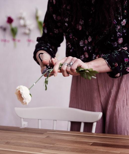 Julia在木檯面修剪人造玫瑰的花莖。