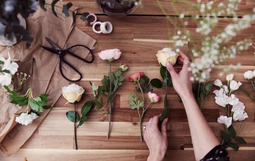 人造花混合真花排列在木檯面上,旁邊放有剪刀和膠紙。
