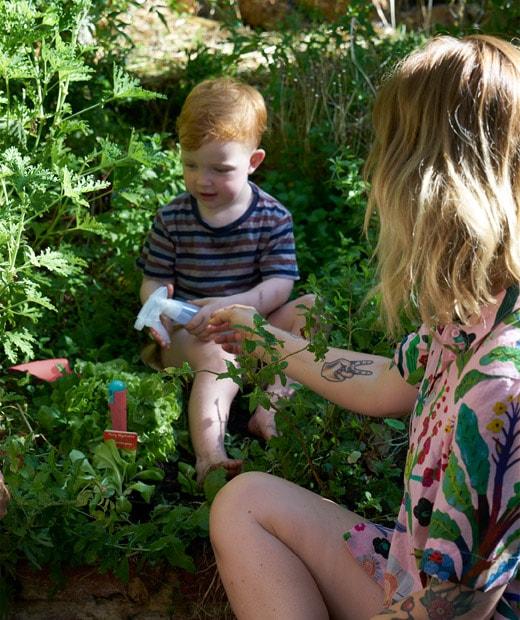 Nici拿著噴水壺幫兒子為植物澆水。
