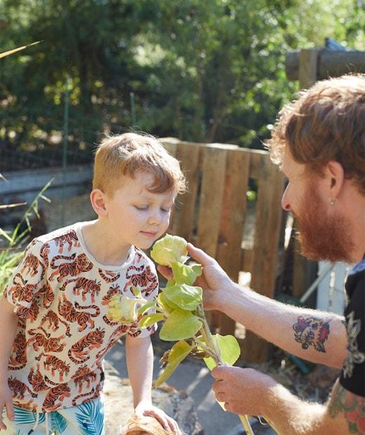 Ben讓兒子在花園體驗花香。