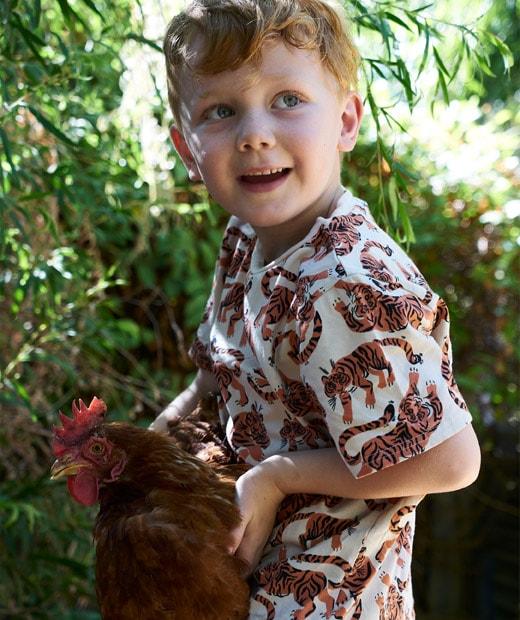 一名小孩拿著一隻雞。