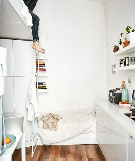 A small all-white apartment with a day bed, mezzanine level and one-wall kitchen.