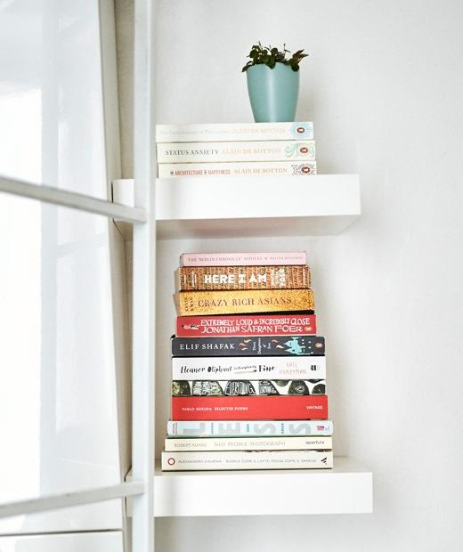 Stacks of books on miniature white shelves.
