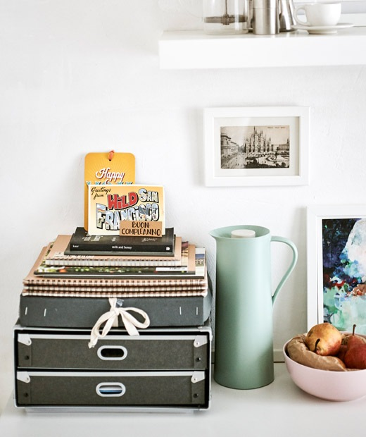 A desk organiser, flask, fruit bowl and pictures arranged as a pretty display.