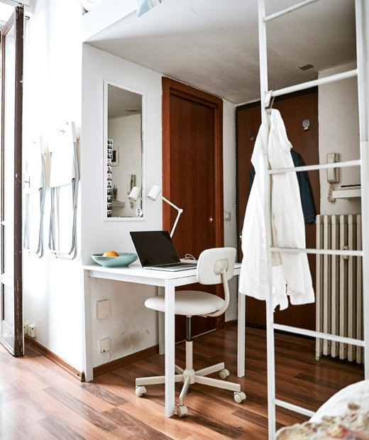 A laptop sits on a desk placed in the space below a mezzanine bed, while a white shirt hangs on a white ladder.