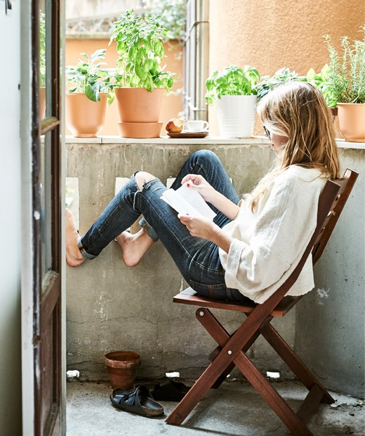 Rhianna坐在戶外露台的摺疊式木椅閱讀,露台放滿盆栽。