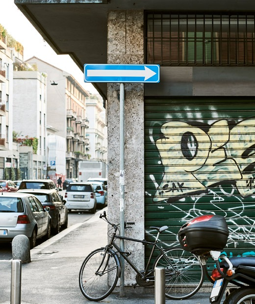 An urban street with parked cars and a bicycle leaning up against a wall with graffiti on it.