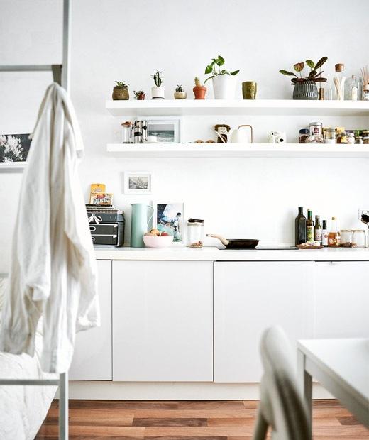 全白色廚房配以開放式層架,前方設有睡床的樓梯。