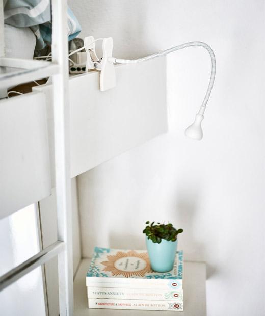 白色活動夾燈指向層架上的一堆書。