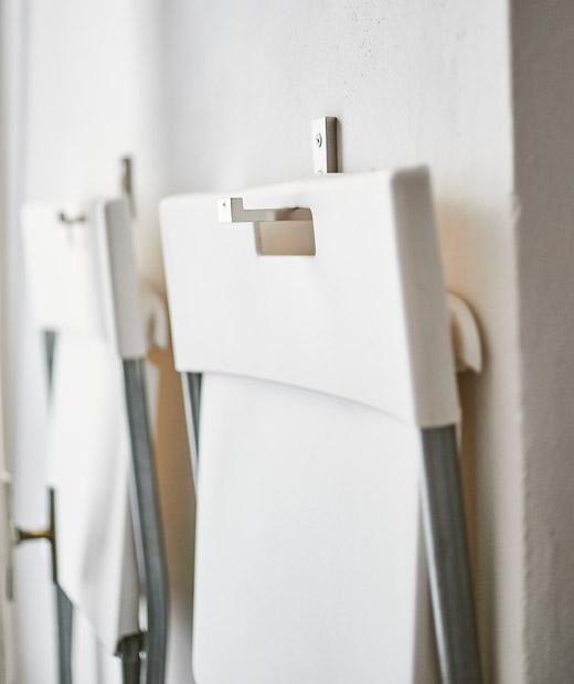 兩張白色摺椅用掛鈎掛在牆上。
