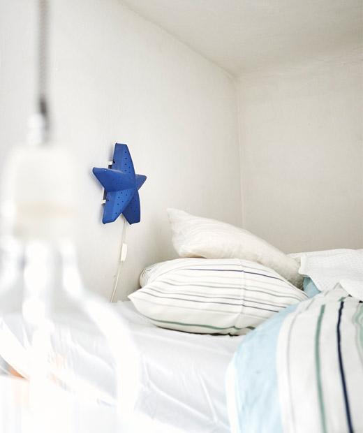 床上鋪上印花寢具,牆上裝有藍色星形壁燈。