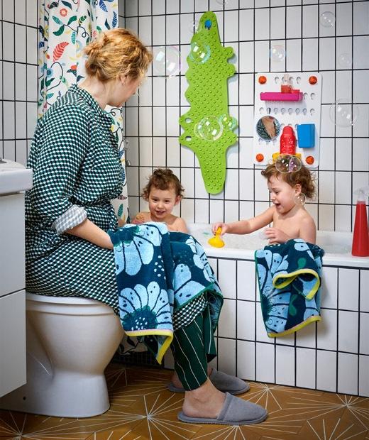 兩名孩子在舖上白色瓷磚的浴缸裡洗澡,一名女子坐在旁邊座廁的蓋子上。