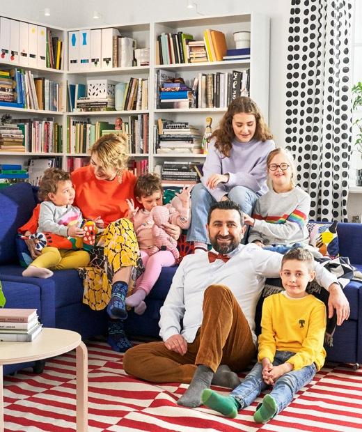 一個大家庭坐在藍色角位梳化上,後面放有書架。