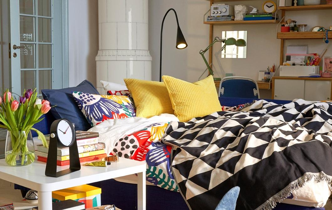 在客廳和工作空間有一張打開的梳化床,配以白色座地燈和茶几。