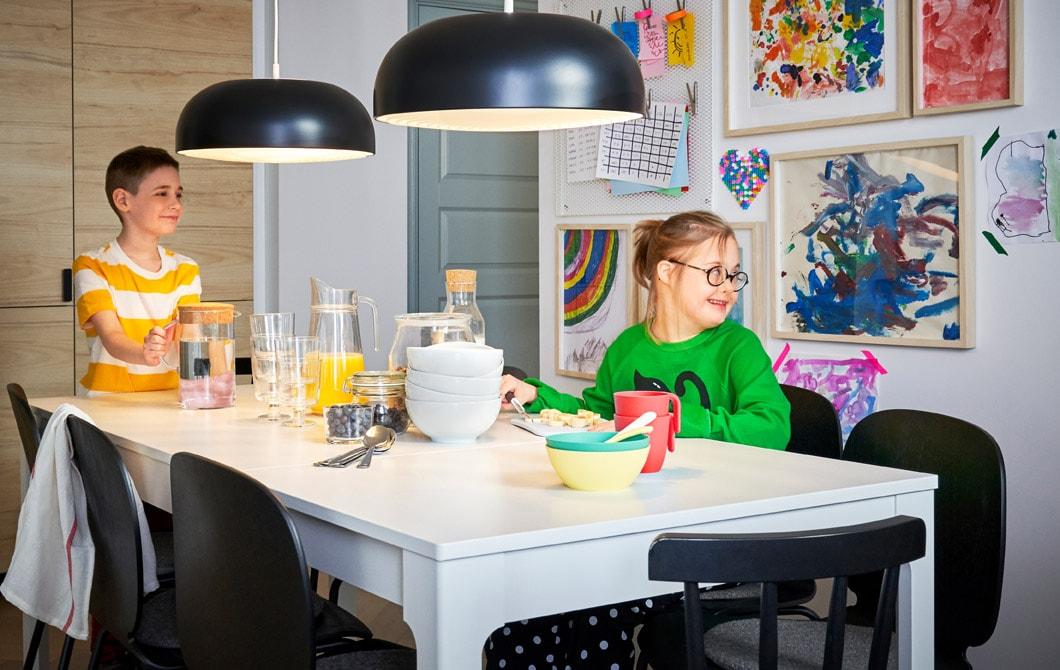 兩名孩子坐在一張白色的大餐檯旁,餐檯上掛著黑色吊燈,身後的牆上掛滿孩子的作品。