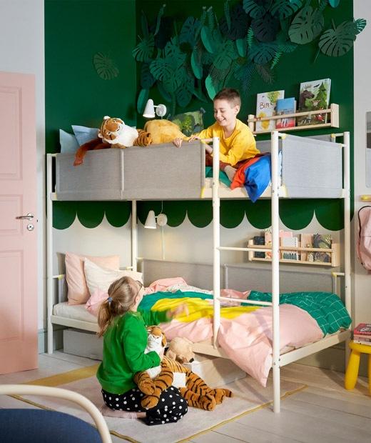 兩名孩子在綠色和白色兒童睡房裡,房內設有碌架床和上牆書架。
