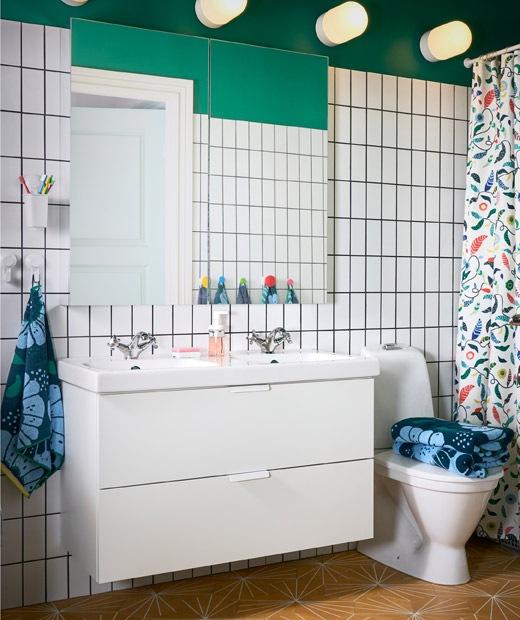 一間鋪有白色瓷磚的綠色浴室,白色雙洗手盆附有兩個抽屜,上面設有一面大鏡子。
