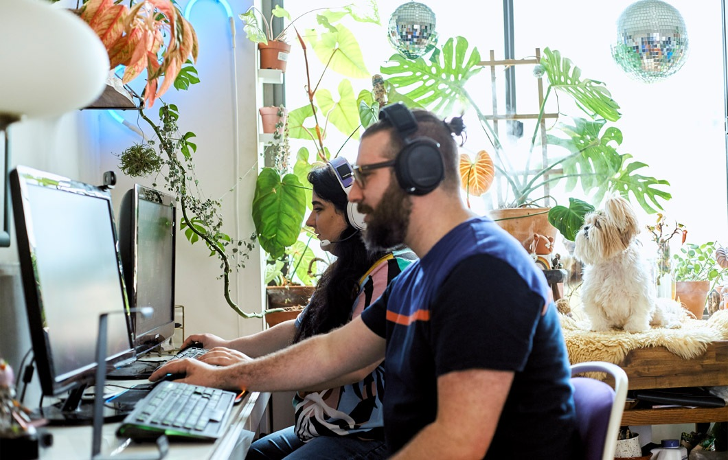 在一個有開放式層架、植物布置和小狗的工作間裡,一男一女在玩電腦遊戲。