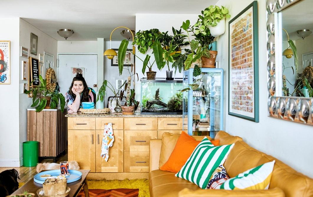 放滿植物的開放式家居裡有廚房島形工作檯、魚缸、梳化、咕𠱸、茶几和牆壁布置。