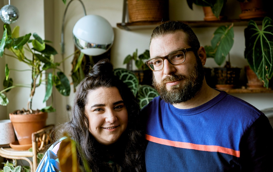 一對年輕情侶在城市公寓裡,身後有許多植物。
