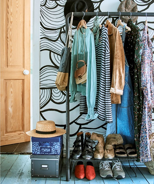 Tops, dresses and jackets hanging on a clothes rail with storage boxes piled beside it and shoes on a rack below it.