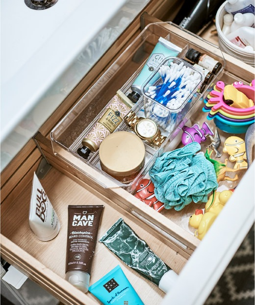 An open drawer in a bathroom vanity unit, with compartments containing a mix of creams, toys and make-up.