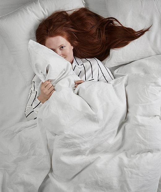 A woman with long red hair and striped pyjamas lies awake on her back in a double bed, clutching a duvet.