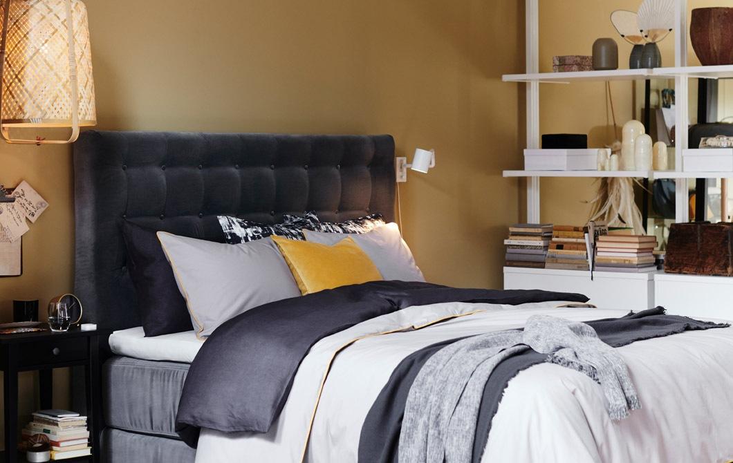 配以灰色絲絨絎縫床頭板的睡床,床上舖上多層寢具。