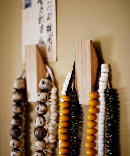 彩色珠子頸鏈掛在兩個木掛鈎上。