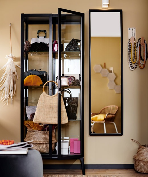 黑色框玻璃門貯物櫃放滿手袋和配飾,旁邊有一面鏡子。