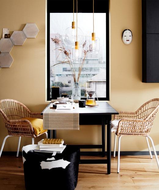 窗前的餐檯旁有兩張藤椅,前面放有一張腳凳,上方有玻璃吊燈。