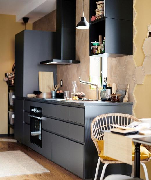 黑色開放式廚房,抽油煙機掛在淺黃色的牆上。