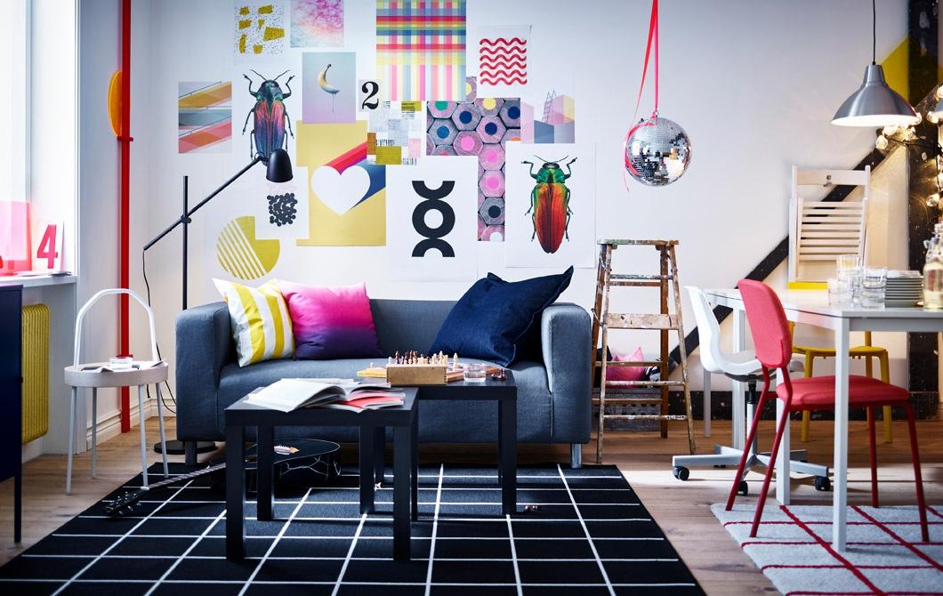 色彩繽紛的客廳和工作間,牆上貼有藝術品,另外放有梳化、茶几、座地燈、白色檯、椅子、地氈和舊木梯。