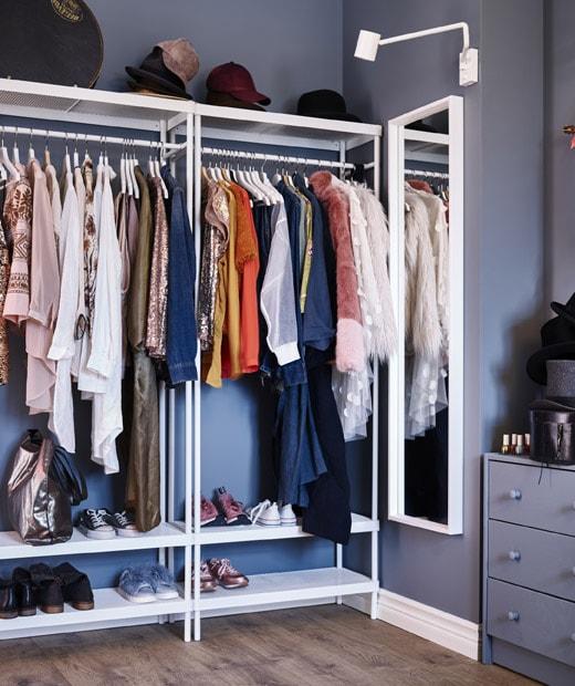 由掛衣桿組成的自訂衣櫃空間,上層放有帽子,底下擺放鞋履,另外還有掛牆鏡、壁燈和抽屜櫃。