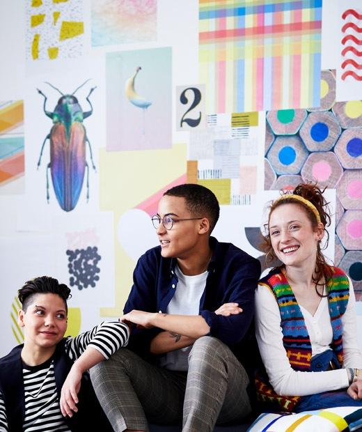 三位住客坐在滿佈彩色圖畫的牆前。