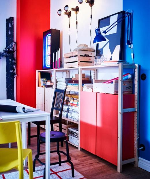 紅色、白色和藍色的牆前有松木層架和貯物組合,前面有白色檯的一角和各款椅子和凳。