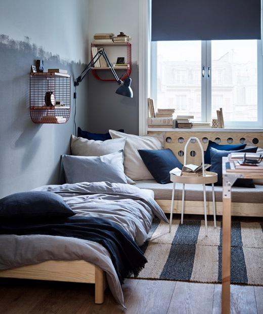 設有角位梳化和單人床的房間,採用深藍色、灰色和天然色調布藝產品,牆上有紅色鐵網貯物架。