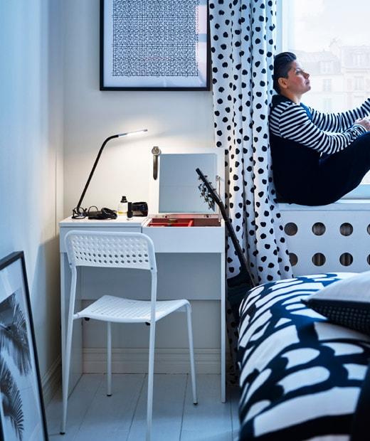 黑白色波點主題睡房,配以白色書檯、椅子和塗漆地板,一名女士坐在窗邊。